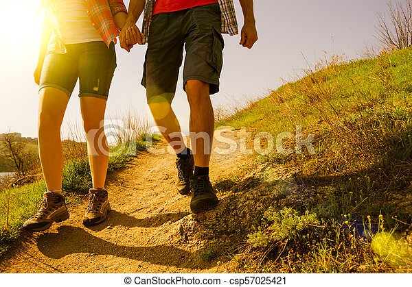 Young Couple Hiking with Backpacks on the Beautiful Rocky Trail at Sunny Evening. Family Travel and Adventure. - csp57025421