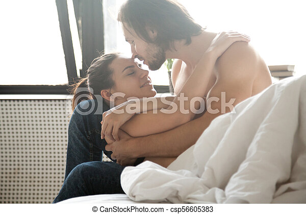 Young Couple In Love Embracing Relaxing On Bed Enjoying Tenderne