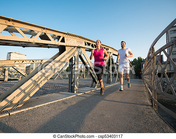 young couple jogging across the bridge in the city - csp53403117
