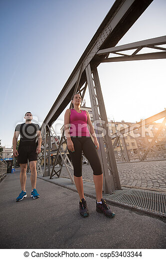 young couple jogging across the bridge in the city - csp53403344
