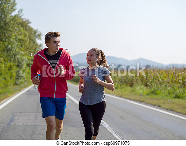 young couple jogging along a country road - csp60971075