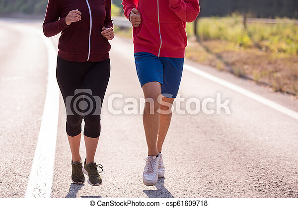 young couple jogging along a country road - csp61609718