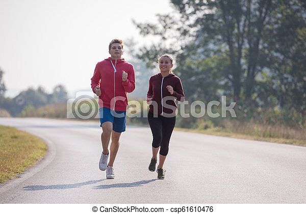 young couple jogging along a country road - csp61610476