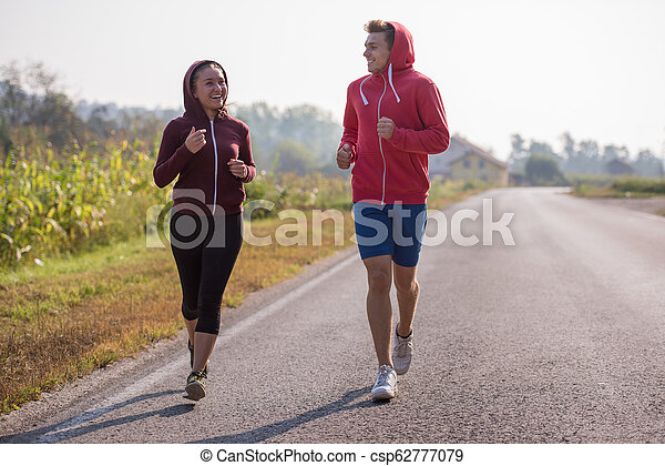 young couple jogging along a country road - csp62777079