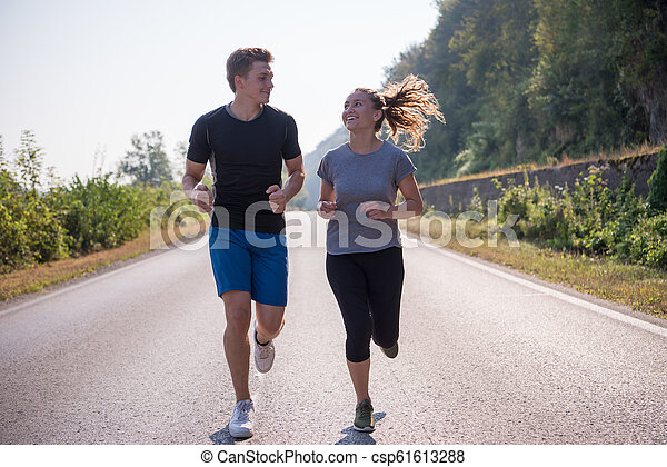 young couple jogging along a country road - csp61613288
