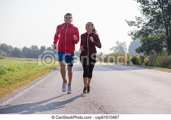 young couple jogging along a country road - csp61610467