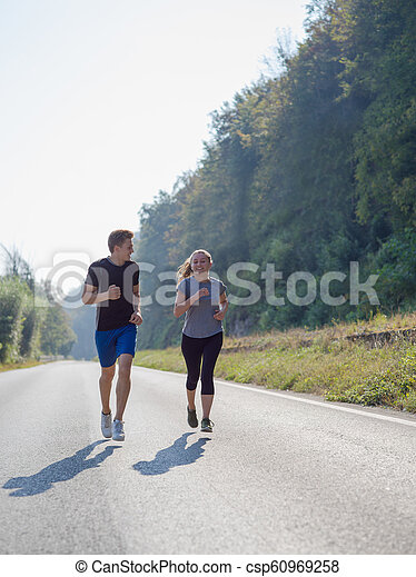 young couple jogging along a country road - csp60969258