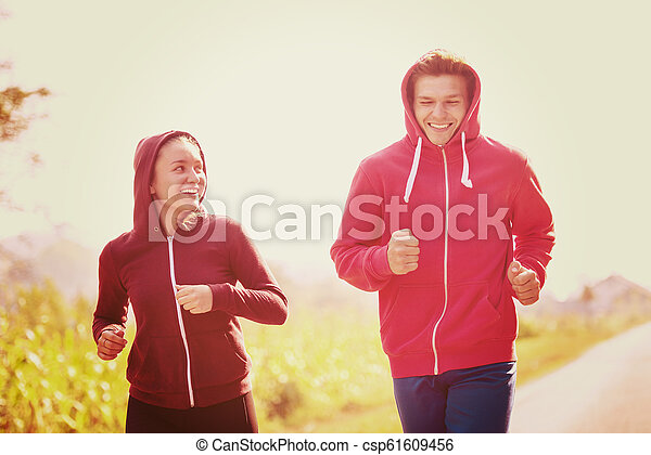 young couple jogging along a country road - csp61609456