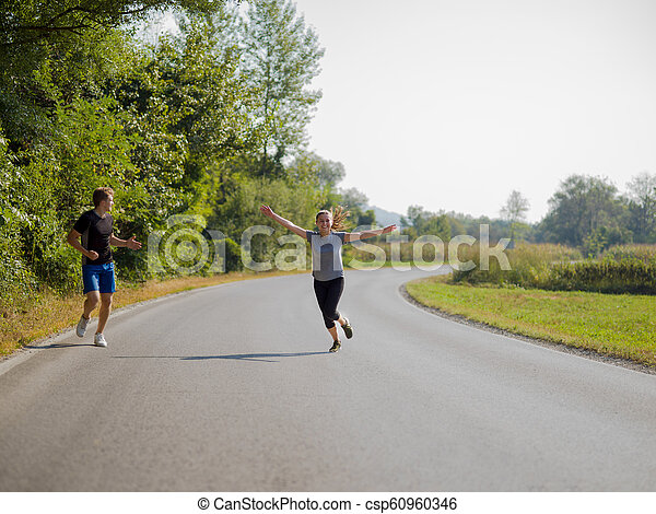 young couple jogging along a country road - csp60960346