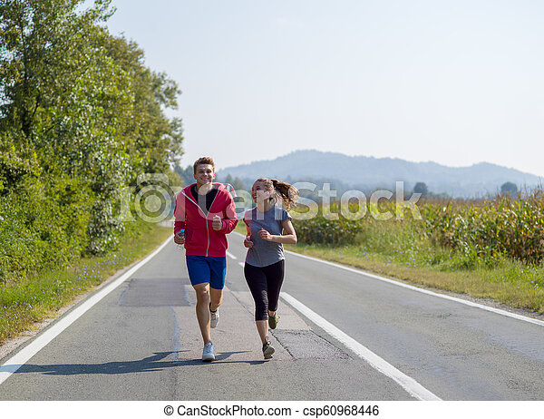 young couple jogging along a country road - csp60968446