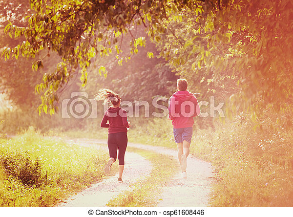 young couple jogging along a country road - csp61608446