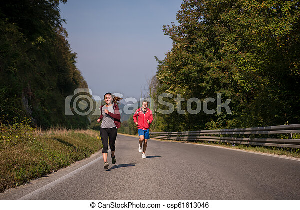 young couple jogging along a country road - csp61613046