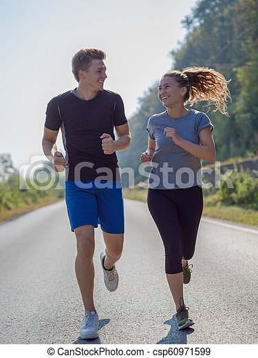 young couple jogging along a country road - csp60971599