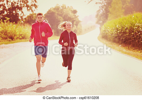 young couple jogging along a country road - csp61610208