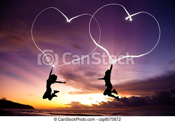 young couple jumping and drawing connected hearts by flashlight in the air on the beach before sunrise - csp8070872