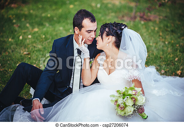 Young couple kissing in wedding gown. Bride holding bouquet of flowers - csp27206074