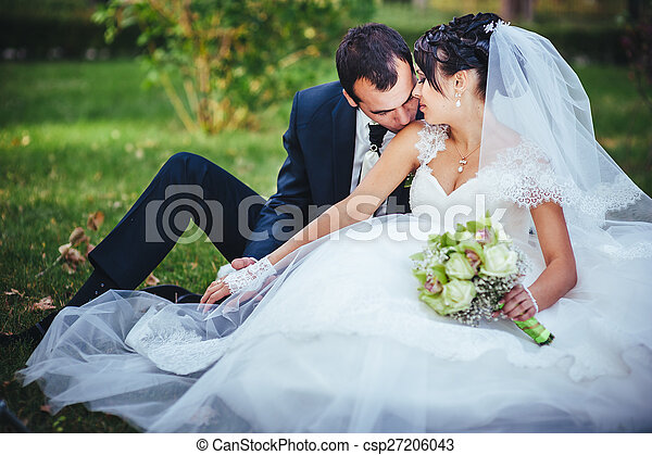 Young couple kissing in wedding gown. Bride holding bouquet of flowers - csp27206043