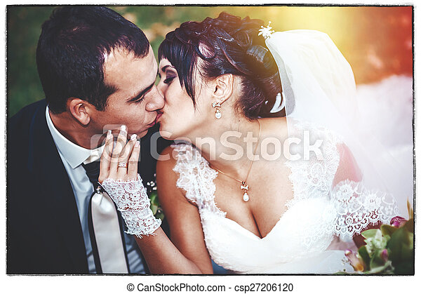 Young couple kissing in wedding gown. Bride holding bouquet of flowers - csp27206120
