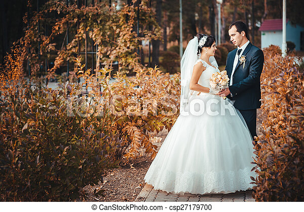 Young couple kissing in wedding gown. Bride holding bouquet of flowers - csp27179700