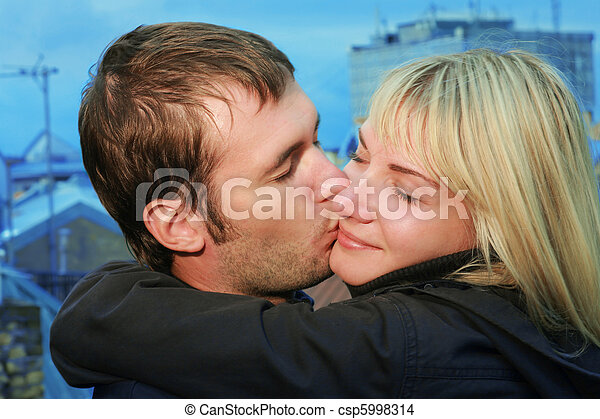 Young couple kissing on a roof in an old European city - csp5998314