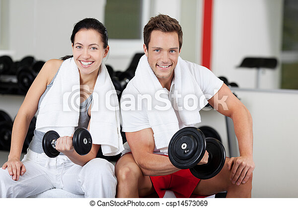 Young Couple Lifting Dumbbells In Gym - csp14573069