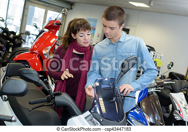 Young couple looking at modern scooter - csp43447183