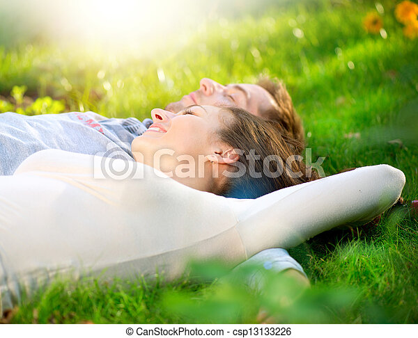 Young Couple Lying on Grass Outdoor  - csp13133226