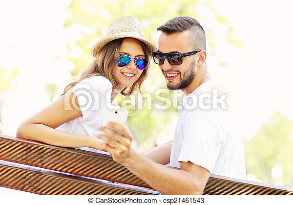 Young couple on a bench with smartphone - csp21461543