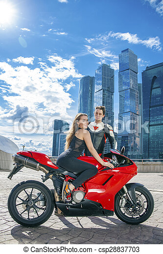 Young couple on a sports bike on the background of the city skyline csp28837703