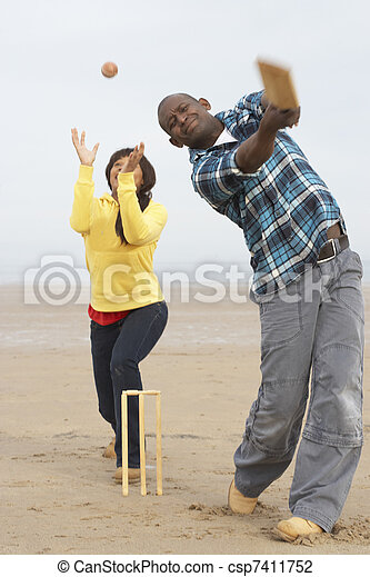 Young Couple Playing Cricket On Autumn Beach Holiday - csp7411752