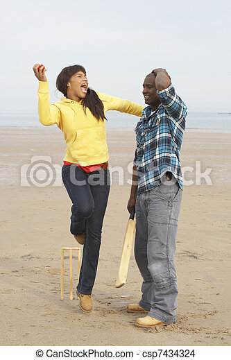 Young Couple Playing Cricket On Autumn Beach Holiday - csp7434324