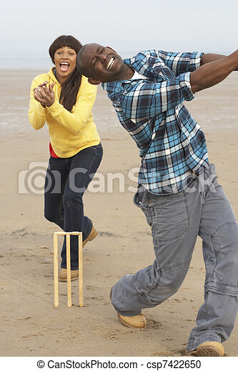 Young Couple Playing Cricket On Autumn Beach Holiday - csp7422650