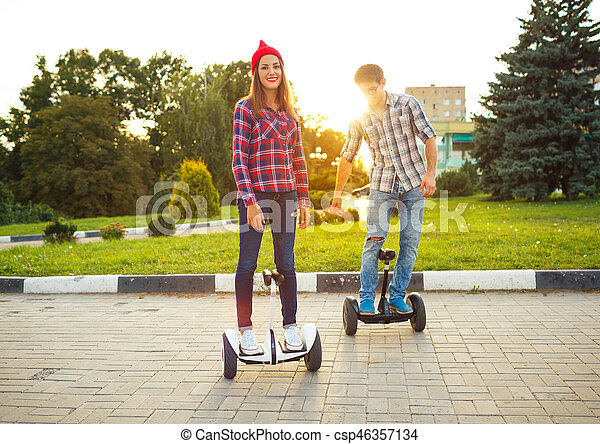 Young couple riding hoverboard - electrical scooter, personal eco transport, gyro scooter, smart balance wheel - csp46357134