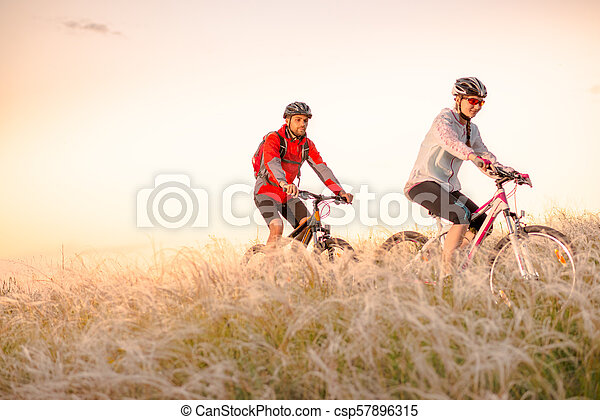 Young Couple Riding Mountain Bikes in the Beautiful Field of Feather Grass at Sunset. Adventure and Family Travel. - csp57896315
