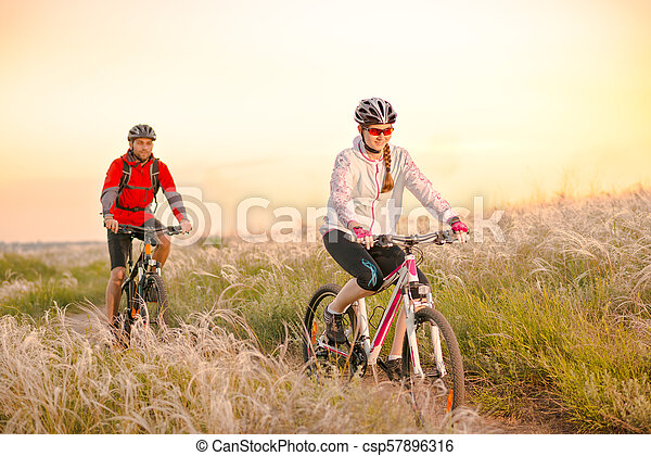 Young Couple Riding Mountain Bikes in the Beautiful Field of Feather Grass at Sunset. Adventure and Family Travel. - csp57896316