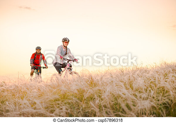 Young Couple Riding Mountain Bikes in the Beautiful Field of Feather Grass at Sunset. Adventure and Family Travel. - csp57896318