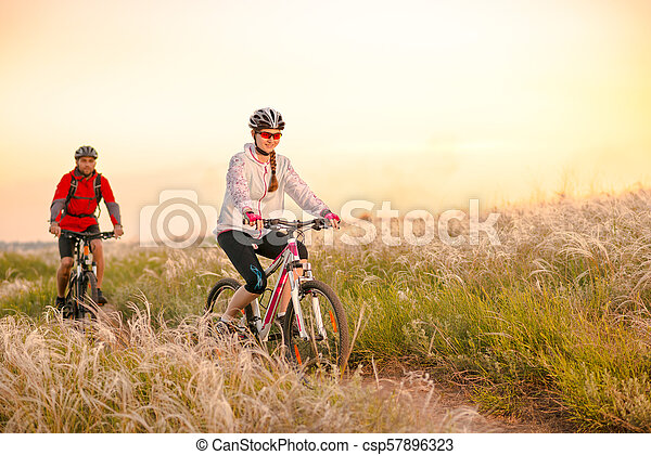Young Couple Riding Mountain Bikes in the Beautiful Field of Feather Grass at Sunset. Adventure and Family Travel. - csp57896323