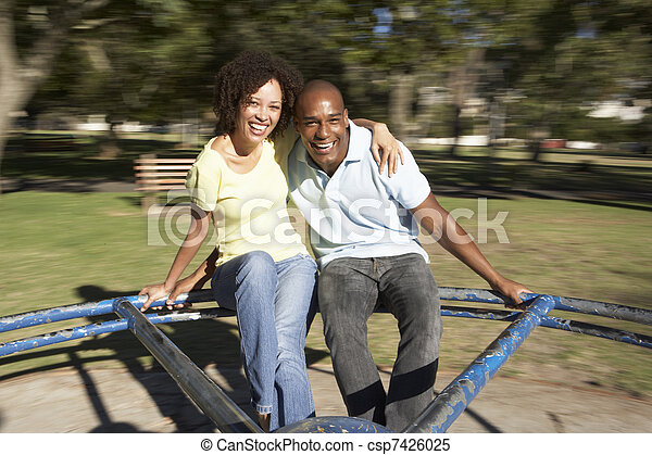Young Couple Riding On Roundabout In Park - csp7426025