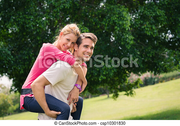 young couple running piggyback in city park - csp10301830