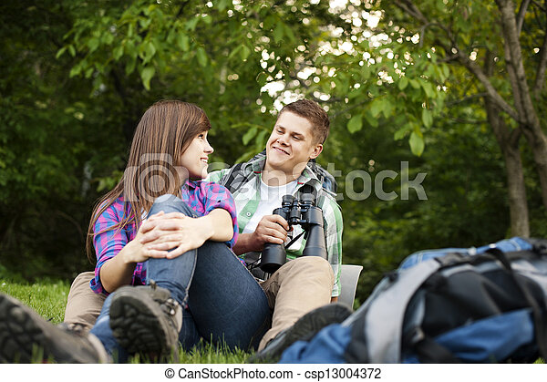 Young couple sitting on glade - csp13004372