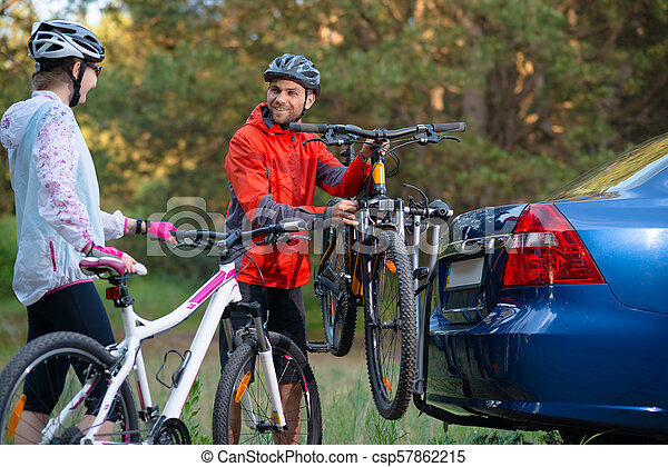Young Couple Unmounting Mountain Bikes from Bike Rack on the Car. Adventure and Family Travel Concept. - csp57862215