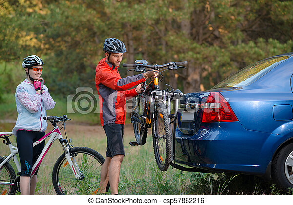 Young Couple Unmounting Mountain Bikes from Bike Rack on the Car. Adventure and Family Travel Concept. - csp57862216