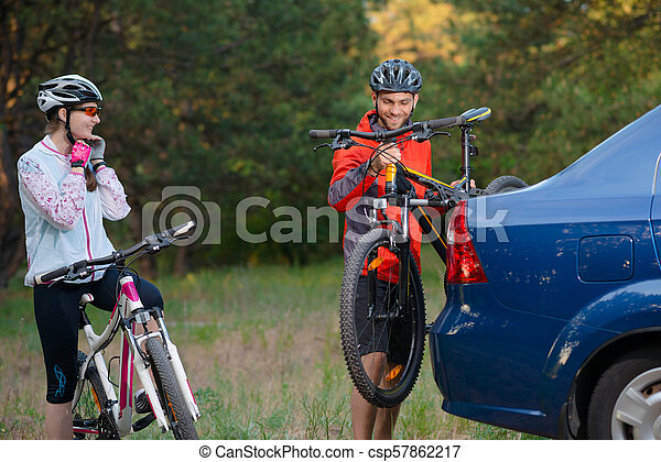 Young Couple Unmounting Mountain Bikes from Bike Rack on the Car. Adventure and Family Travel Concept. - csp57862217