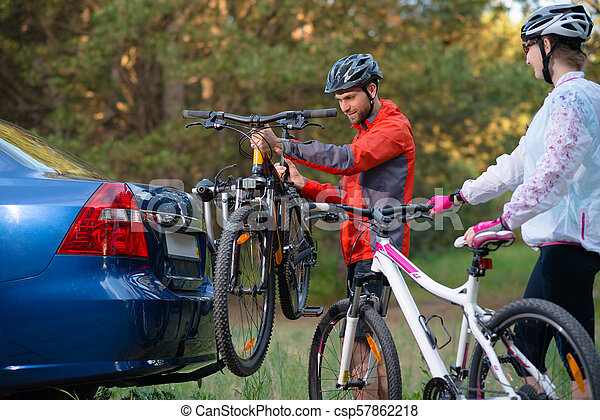 Young Couple Unmounting Mountain Bikes from Bike Rack on the Car. Adventure and Family Travel Concept. - csp57862218