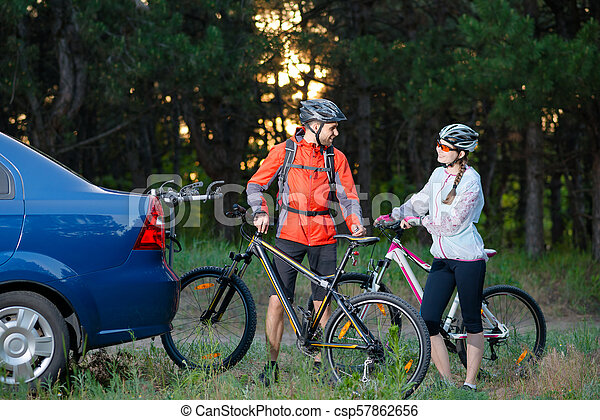 Young Couple Unmounting Mountain Bikes from Bike Rack on the Car. Adventure and Family Travel Concept. - csp57862656