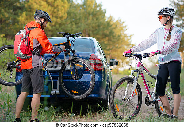 Young Couple Unmounting Mountain Bikes from Bike Rack on the Car. Adventure and Family Travel Concept. - csp57862658