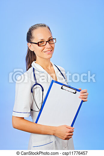 Young cute woman doctor holding copyspaced clipboard waist-high portrait on blue - csp11776457