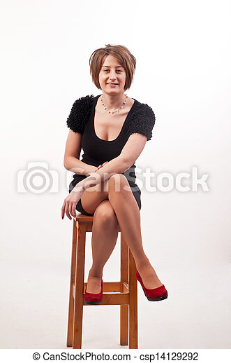 young elegant woman in black dress sitting on chair - csp14129292