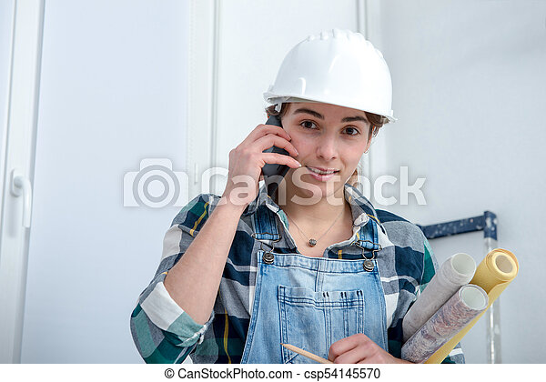 young engineer woman with safety hard hat talking on phone a young