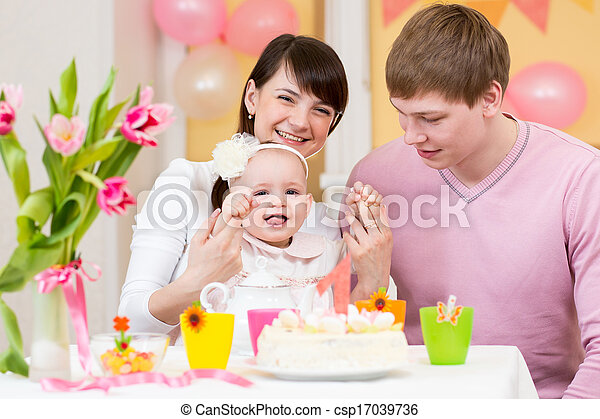 young family celebrating first birthday of baby girl - csp17039736
